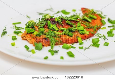 Fried pork schnitzel with greens on white plate