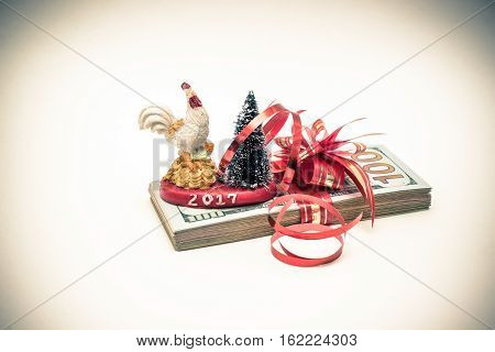 Symbol 2017-cock stands on a pack of American currency