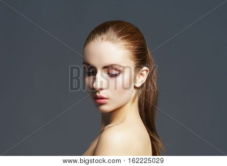 Beauty close-up portrait of beautiful, fresh and healthy girl. Human face over grey background.