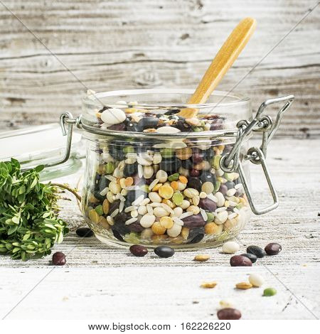 Assorted legumes different cereals in a glass jar with a lid and a wooden spoon on a light background with a bunch of thyme. selective focus