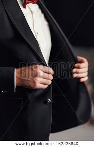Man with red bow tie buttons up his black blazer