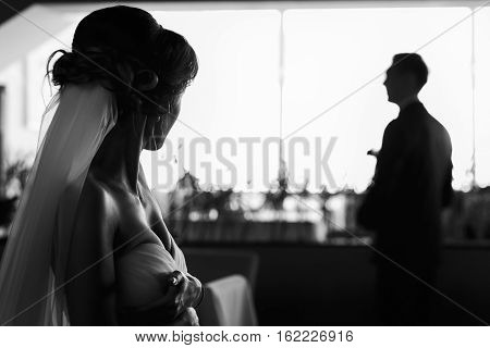 Bride Looks At Fiance Who Is Standing In The Front Of The Window