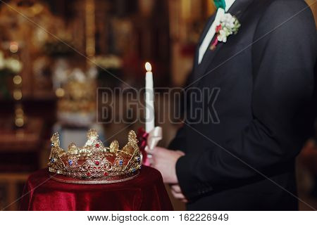 Crown lies on the red velvet while bridegroom stands on the background with candle
