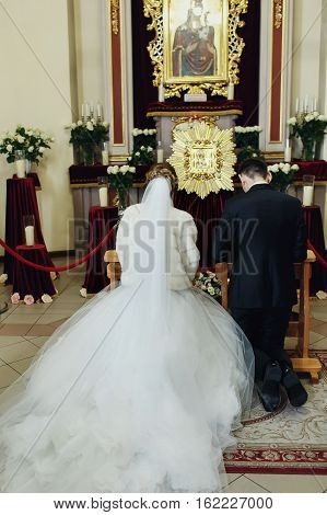 Newlyweds Pray On Kneels In The Front Of Icon In The Church