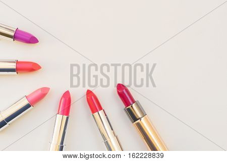 Collection of puple, pink and red shiny lipsticks, flat lay top view with copy space
