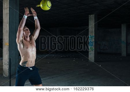 Young strong man throwing weight up while standing in abandoned building. Horizontal indoor shot