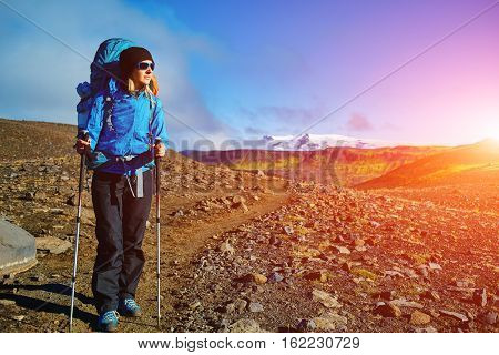 woman hiker on the trail in the Islandic mountains. woman standing and posing against the backdrop of a desert mountain landscape. Treking in National Park Landmannalaugar, Iceland. Travel photography concept poster