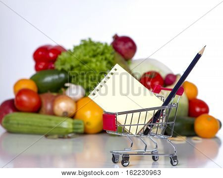 Plan your shopping list in a food shop - trolley with a notebook in the foreground. saving concept