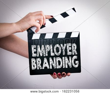 Employer Branding. Female hands holding movie clapper.