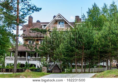 Valdaysky District, Russia - June 16, 2013: Large three-storey log house with veranda in the classical Russian style in the meadow among the trees by Andrey Kopylov, aka linkpusher