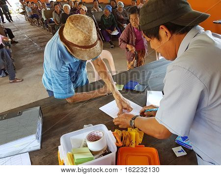 CHIANG RAI THAILAND - DECEMBER 19 : Unidentified asian old man fingerprinting on paper before treatment on December 19 2016 in Chiang rai Thailand.