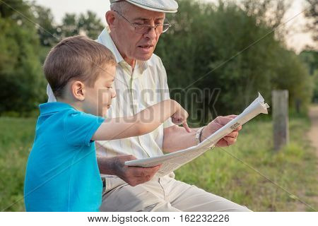 Closeup of senior man reading newspaper and cute child pointing an article with his finger over a nature background. Two different generations concept.