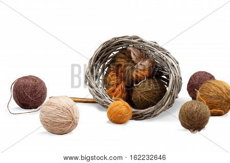 Colorful yarn in tangle and coil in overturned braided basket near tangles of yarn and wooden spokes. isolated on white