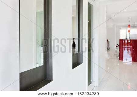 Interior hallway of a modern mansion or hotel expressing close view of a door and two windows on the outside wall of a room there are floor tiles gives a shining view to the house. A hallway for inside
