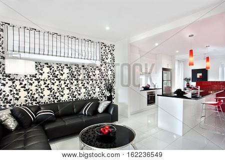 Modern living room interior designed by black vine which on the wall next to the kitchen. There are red lights hanging over the sink of the shiny black counter top next to the chair. The black sofa with pillows near the round black table