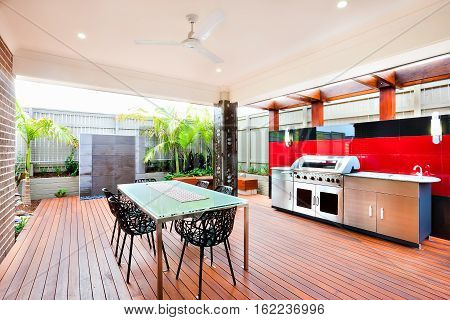 Modern and relaxing area of a luxury house whole area covers with wooden walls pillars and a fence chairs are made using a beautiful carve on the wooden floor there There is a silver color gas grill cabinet near black and red wall tiles.