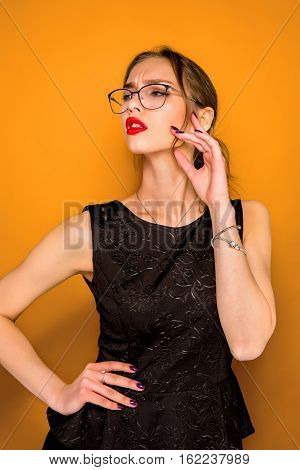 The young woman's portrait with wary emotions on orange studio background