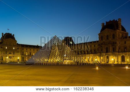 PARIS, FRANCE - DECEMBER 4, 2016: View of famous Louvre Museum with Louvre Pyramid at evening. Louvre Museum is one of the largest and most visited museums worldwide.