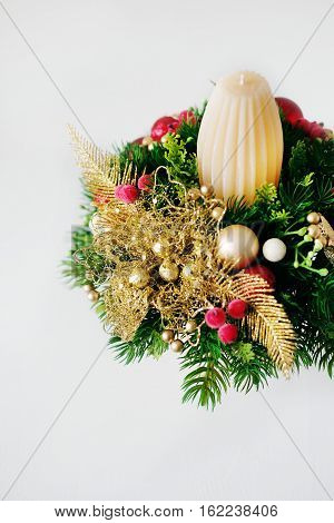Christmas holiday centerpiece decor with fir branches golden leaves red berries and white candle