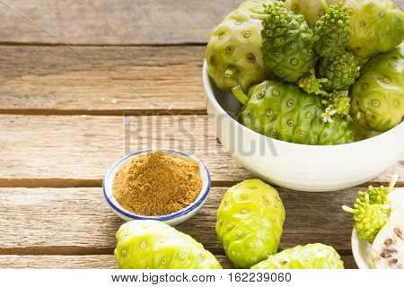 Noni fruit  and  noni bowl with noni powder on wooden table.Fruit for health and herb for health.