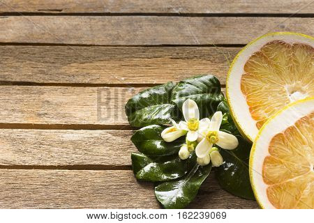 Pomelo slice and blossom on wooden table.Zoom in