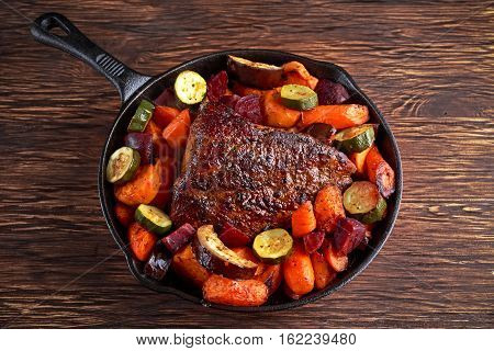 Oven baked Juicy pork loin with vegetables in griddle rustic pan.
