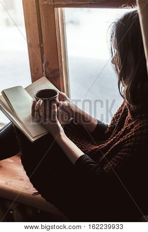 Pre teen child in warm woolen sweater seating on window sill, drinking tea and reading a book. Winter weekends in old log house. Cold snowy weather. Cozy homely concept.