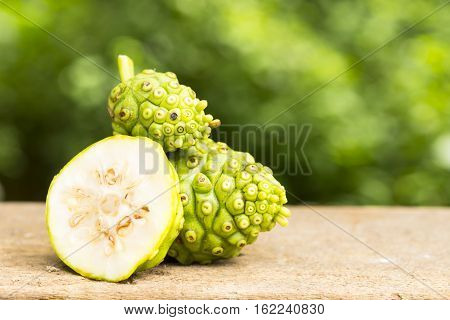 Noni fruit and noni slice on wooden table and green background.Fruit for health and herb for health.110