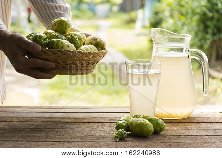 Noni fruit  and noni juice and noni basket on wooden table.And noni in his hand.Zoom in