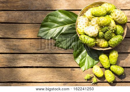 Noni fruit  and noni in the basket on wooden table.Top view
