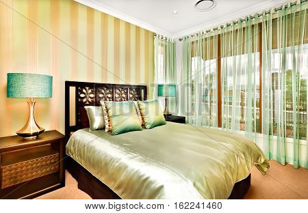 There is a huge king size bed made of wood in a modern room with shiny pillows and sheets on it Glossy brass looking cupboards with shiny table lamps on it. Windows with curtains show the outside