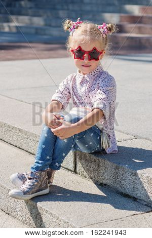 Adorable little girl sitting on stairs on warm and sunny summer day