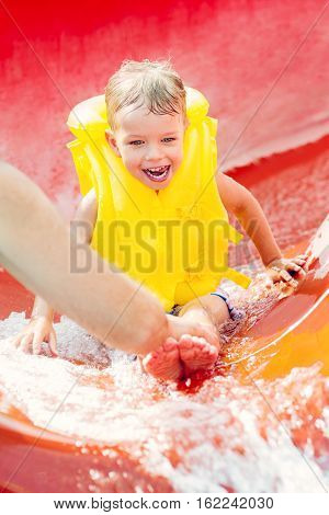 little boy down with a water slide in the inflatable vest