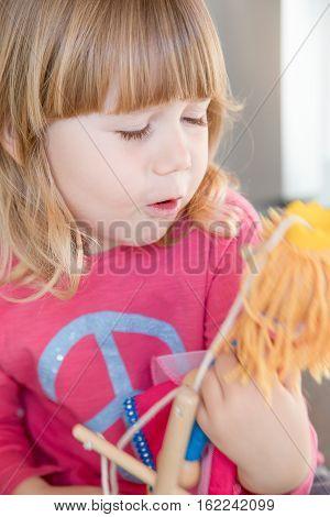 Blonde Child Pink Shirt Talking To Puppet