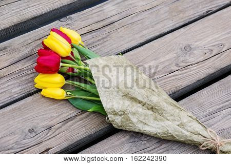 Bunch of fresh spring tulips on old vintage wooden board