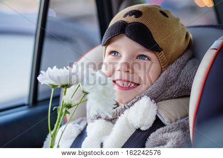 portrait happy toddler boy sitting in the car seat with flowers