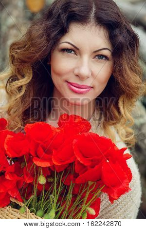 beautiful young woman with a bouquet of poppies spring