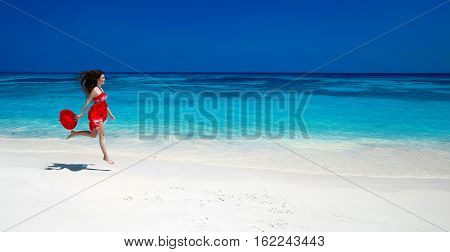 Summer Holiday. Happy Beautiful Woman Jumping On The Exotic Sea. Carefree Brunette Girl In Red Dress