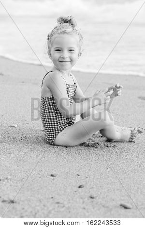 Portrait of a happy charming little girl on the beach ( black and white )