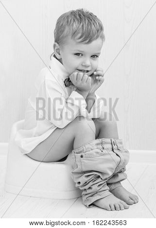 cute smiling child on a pot on a white background ( black and white )