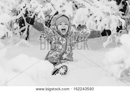 happy little girl playing in the snow sitting ( black and white )