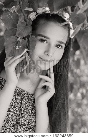 portrait of a beautiful girl of ten years in the green foliage of trees ( black and white )