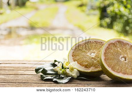 Pomelo slice and blossom on wooden table.Zoom in01