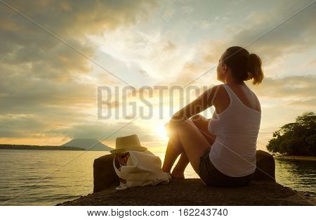 Rear view of happy young woman backpacker sitting on the pier enjoying stunning sunset