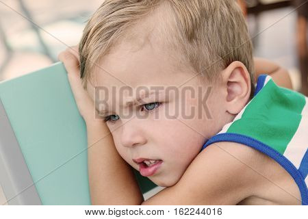 Portrait of upset young boy sitting on a chair outdoors