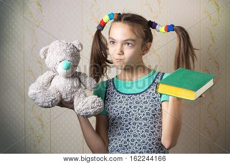11-year-old Girl Holding A Book In One Hand And A Teddy Bear In The Other