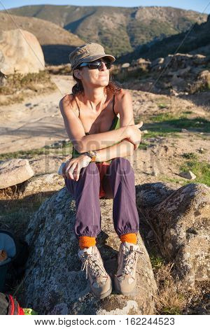 sport pretty woman green shirt purple trousers cap and sunglasses sitting on rock relaxing and posing looking in summer in Gredos mountain Avila Spain Europe