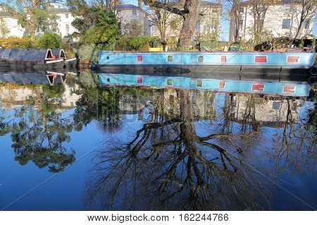 LONDON, UK: Reflections in Little Venice with colorful barges along canals
