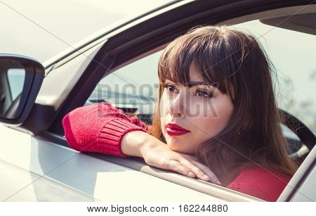 attractive young woman driving a car on a sunny day