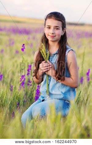 portrait of a sweet young girl in field with spikelets in the hands